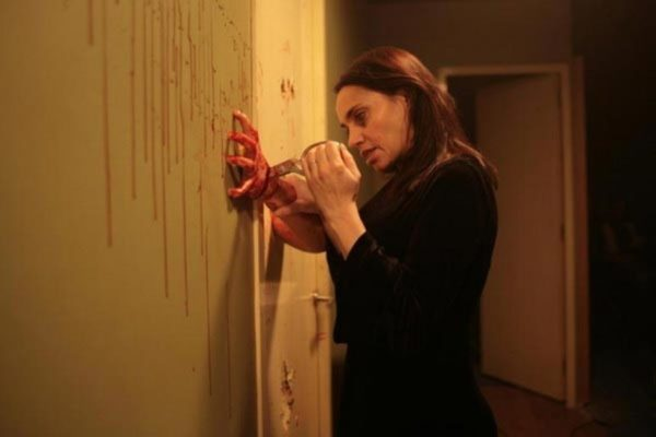 A still of Béatrice Dalle stabbing a hand with a pair of scissors