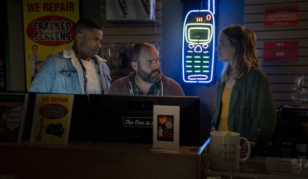 Jordan Calloway, Tom Segura and Elizabeth Lail stand behind a desk in a phone shop