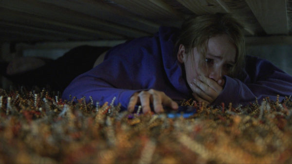 Talitha Eliana Bateman hiding under the bed in Countdown