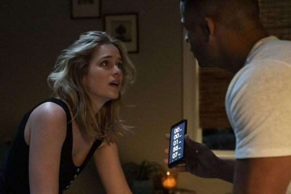 Elizabeth Lail stares at Jordan Calloway holding a phone in Countdown