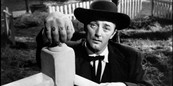 Robert Mitchum as Harry Powell leaning on a doorknob with the letters LOVE exposed on his knuckles