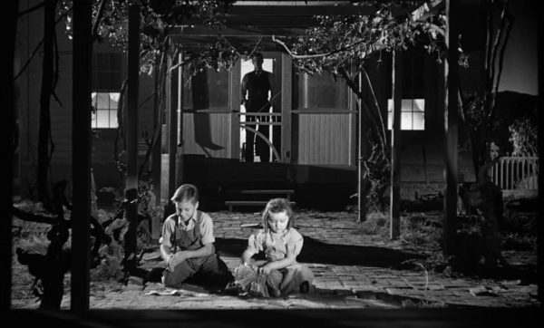 Robert Mitchum as Harry Powell, standing on the porch, looming ominously in the background as two children play in the foreground