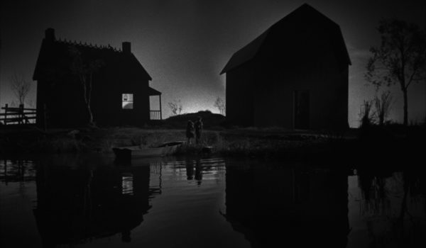 Black and white image of the sun rising in between two house