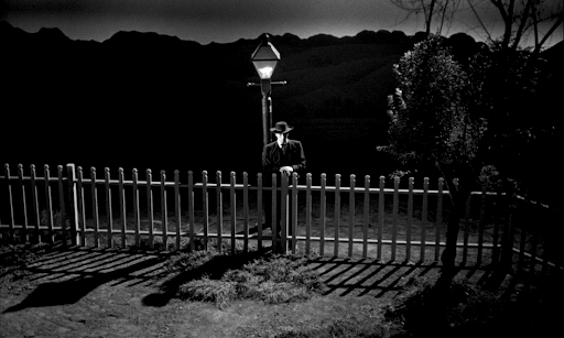 Robert Mitchum as Harry Powell leaning on a fence under a streetlamp