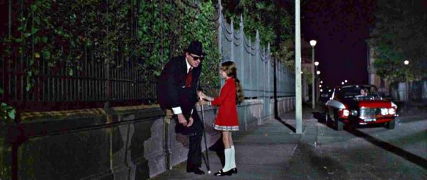 A blind man ties his shoe while a young girl in red dress holds his hand