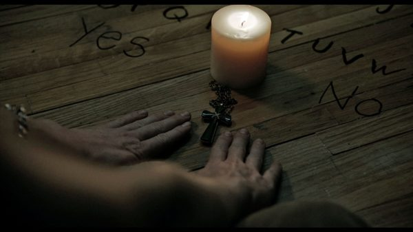 Hands pressed around a crucifix and a candle on a handmade Ouija board on the floor