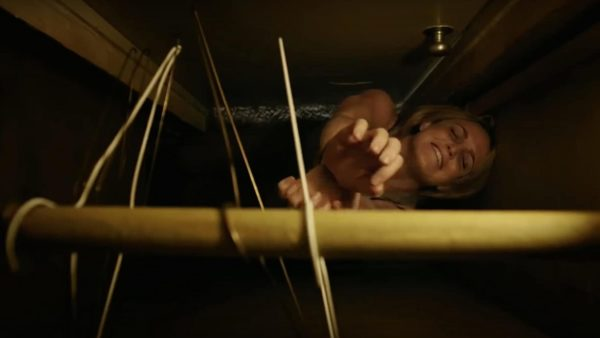 Caity Lotz, her hands bound, reaches up for a wire hanger in a closet high above