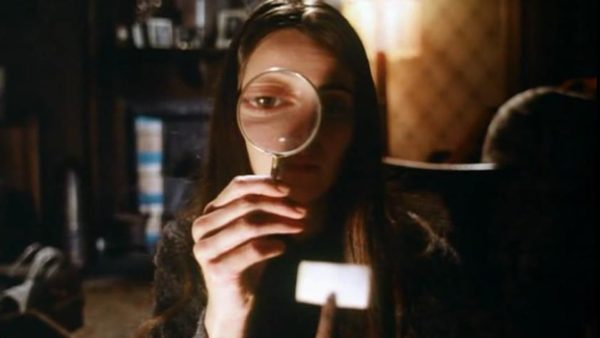 Linda (Jacki Kerin) holds a magnifying glass up to her face