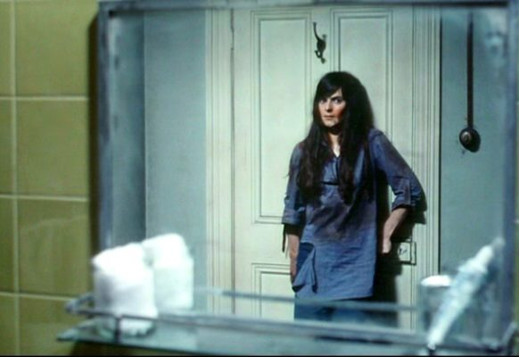 Linda (Jacki Kerin) looks at herself in the mirror as she presses up against the bathroom door, bloodies and desperate