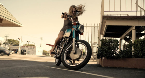 Caity Lotz trying to kick start her motorcycle