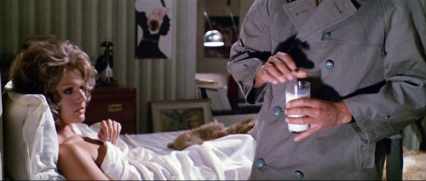 A woman sits upright in bed as the upper body of a man wearing a trench coat holds a glass of milk