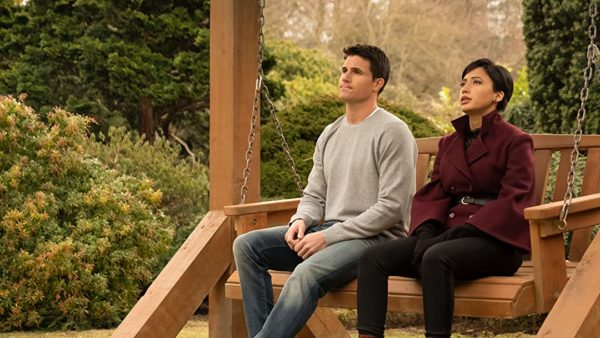 Nathan (Robbie Amell) and Nora (Andy Allo) sit on a bench outside