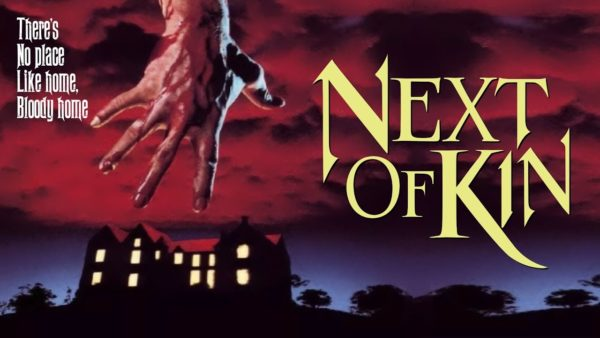 The poster for Next of Kin: a large hand dripping blood reaching down from red clouds towards a mansion with all of the lights on