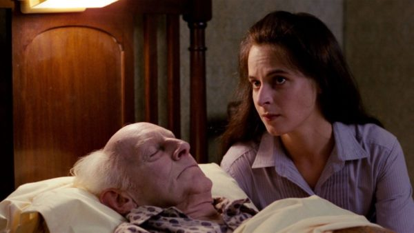 A young woman with dark brown hair sits on the left side of an old man lying in bed with his eyes closed