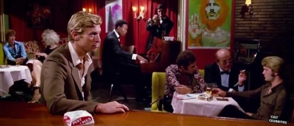 A blonde man sits at a table in a crowded gay bar