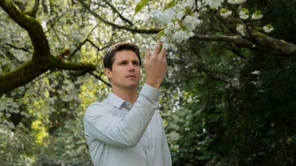 Nathan (Robbie Amell) touches a flower on a tree