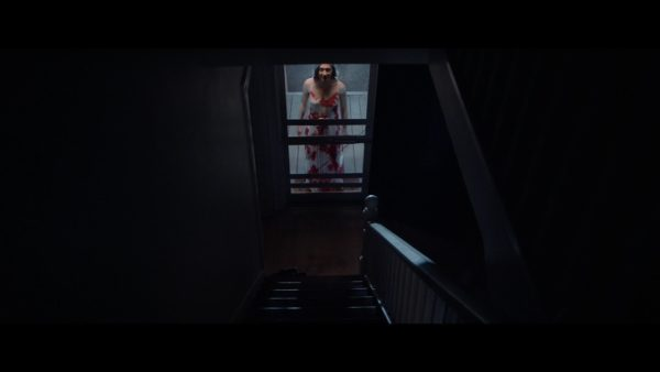 Abby (Zarah Mahler) is seen standing on the porch from a perspective at the top of the stairs