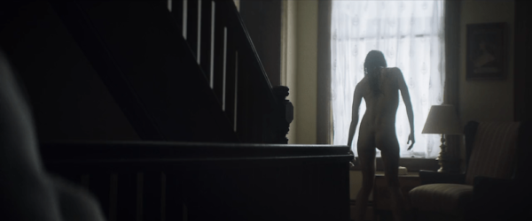 A naked woman stands crookedly in front of a window