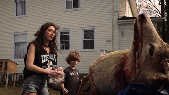 Zarah Mahler as Abby and Blane Crockarell as Dillon stare at the dead body of a buck in the back of a truck