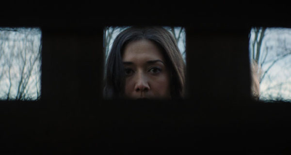 Abby (Zarah Mahler)'s face is framed in a square as she stares into the cellar