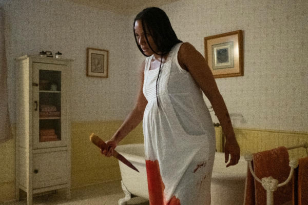 A pregnant woman in a bloody nightgown wields a stake in a bathroom
