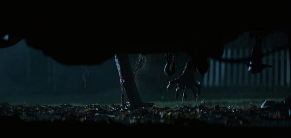 A shot from under a car as a creature crawls out of the driver's seat