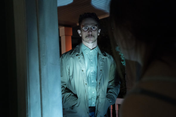 A bespectacled and mustachoed man stands in a doorway in the light of a flashlight
