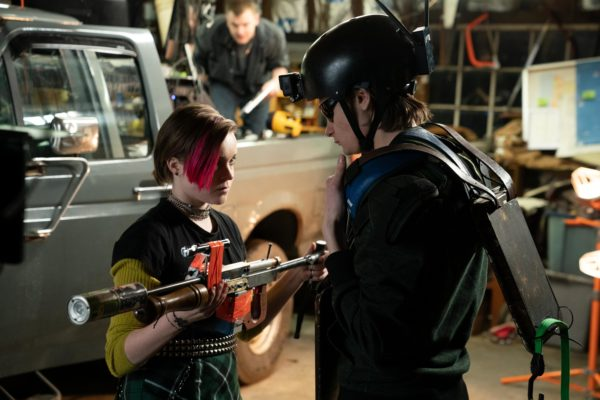 A girl with red streaked hair presents a gun to a boy in armor and helmet