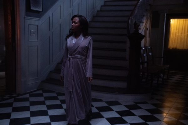 A woman in a nightgown stands at the base of a tall flight of stairs in the dark
