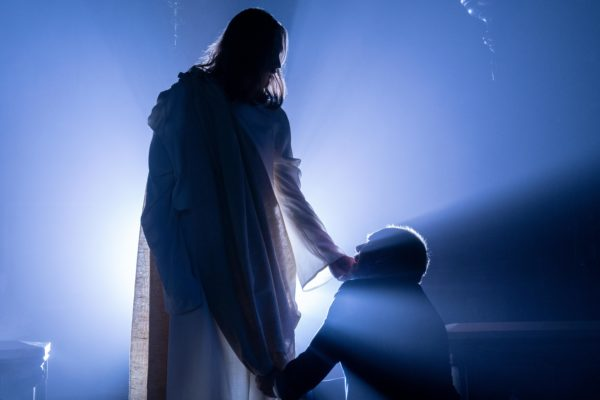 A kneeling man is touched on the chin by Jesus as light shines behind them