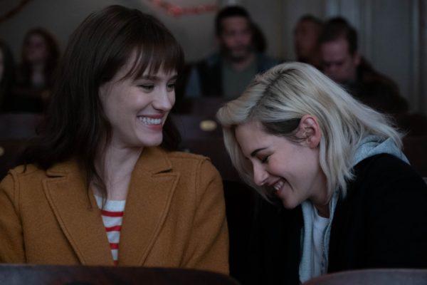 Mackenzie Davis as Harper laughs with Kristen Stewart as Abby in a movie theatre
