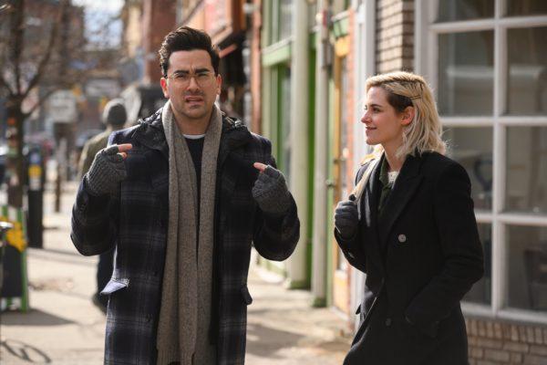 Dan Levy as John stands with Kristen Stewart as Abby on the sidewalk