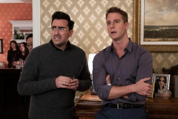 Dan Levy as John and Jake McDorman as Connor watch uncomfortably with drinks in hand