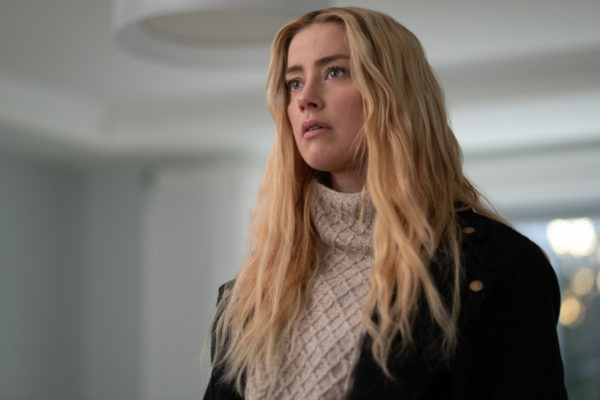 Nadine Cross (Amber Heard), a blonde woman in a knit white sweater and black jacket
