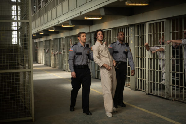 Lloyd Henreid (Nat Wolff) in a white prison jumpsuit is escorted by two guards past a row of cells