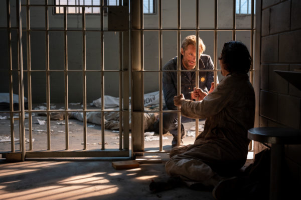 Alexander Skarsgård as Randall Flagg kneels in front of a prison cell