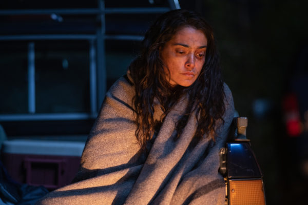 A woman with facial bruises sits in front of a campfire, wrapped in a blanket