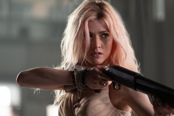 A pink haired woman holds a shotgun