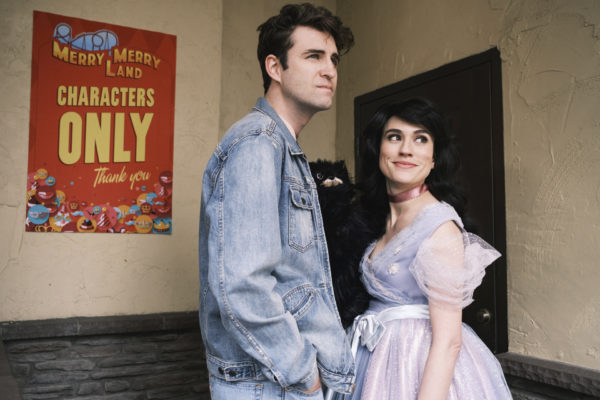 A tall dark haired man in glasses and a jean jacket stands next to a brunette in a princess costume