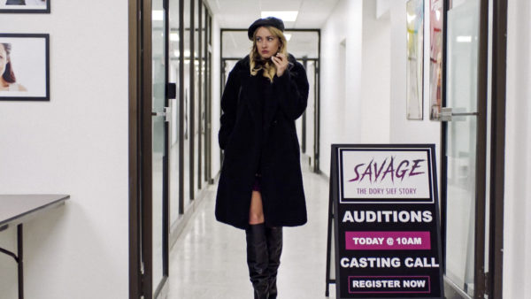 A stylish blonde dressed all in black stands next to a sign that reads SAVAGE auditions
