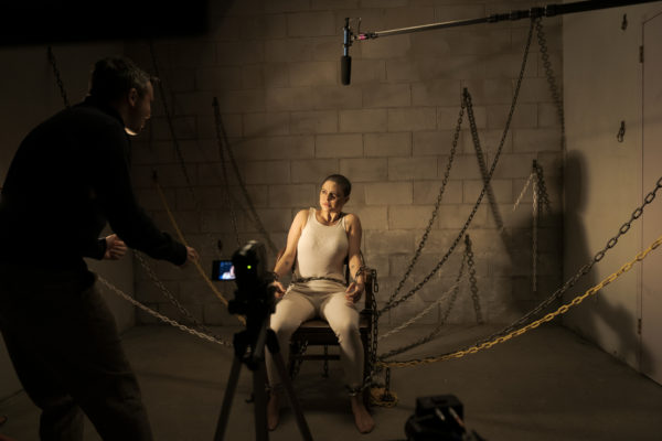 A woman dressed in white with a shaved head is tied to a chair in front of a camera