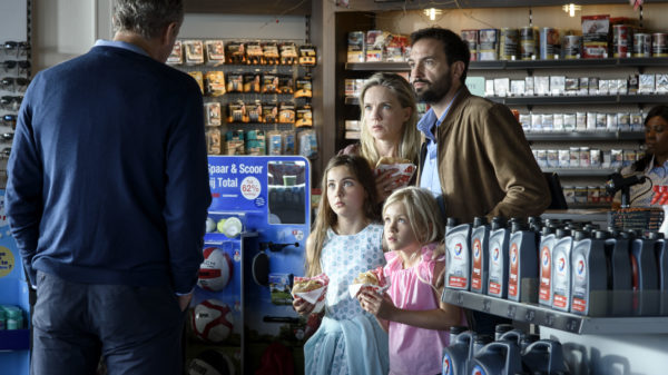 A man, woman and their two daughters are confronted by a tall man in a convenience store