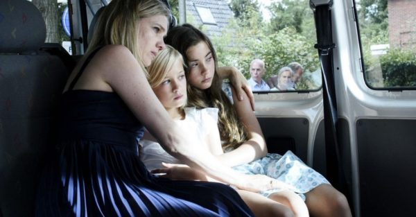 A blonde woman holds her two children in the back of a car
