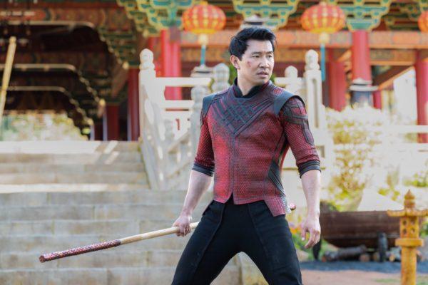 Shang-Chi (Simu Liu) grips a baton in front of a temple