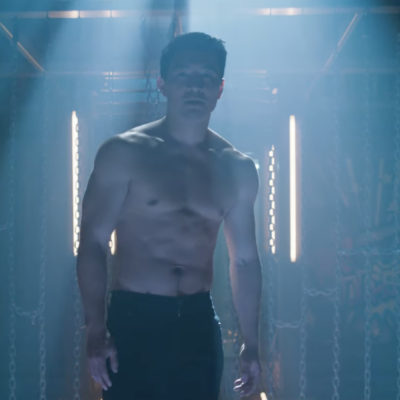 A shirtless man stands in a dimly lit space