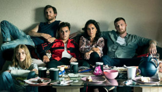 A woman sits on a couch with three men and a teen girl (far left)