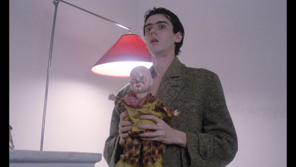A young man in a wool coat clutches a doll