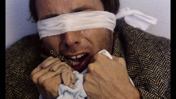 A blindfolded man clutches a blanket to his chin