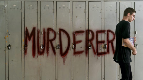 A teen boy walks past a row of lockers with the word MURDERER written in red paint