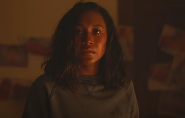 A black teen girl stares at the camera, her face lit a by fire